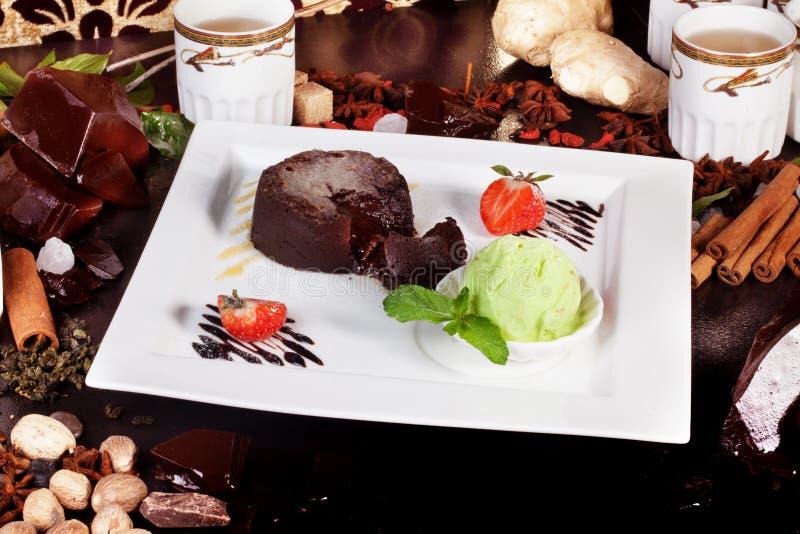 Gâteau de 'brownie' avec des fraises, thé, épices, crème glacée de pistache, l'atmosphère photos stock