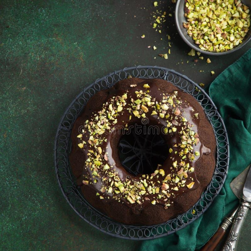 Gâteau de bundt de chocolat avec le lustre et les pistaches de chocolat photographie stock libre de droits