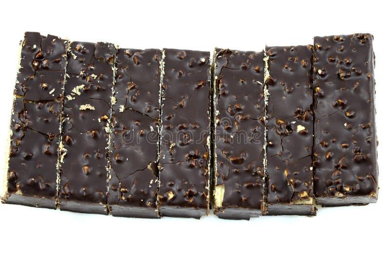 Gâteau de chocolat avec des écrous, coupe en morceaux rectangulaires, sur un fond blanc photos libres de droits