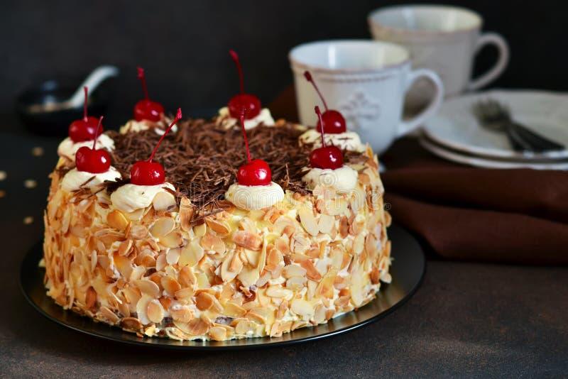 Gâteau de chocolat avec de la crème, la cerise et les amandes de vanille photographie stock libre de droits