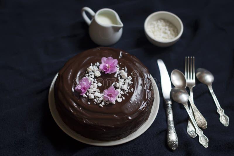 Gâteau de chocolat décoré des miettes et des violettes de meringue photographie stock libre de droits