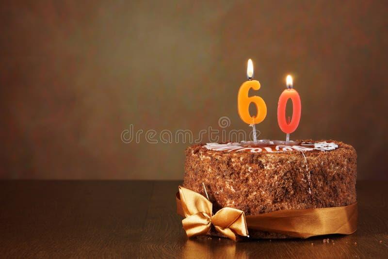 Gâteau de chocolat d'anniversaire avec les bougies brûlantes comme numéro soixante image stock
