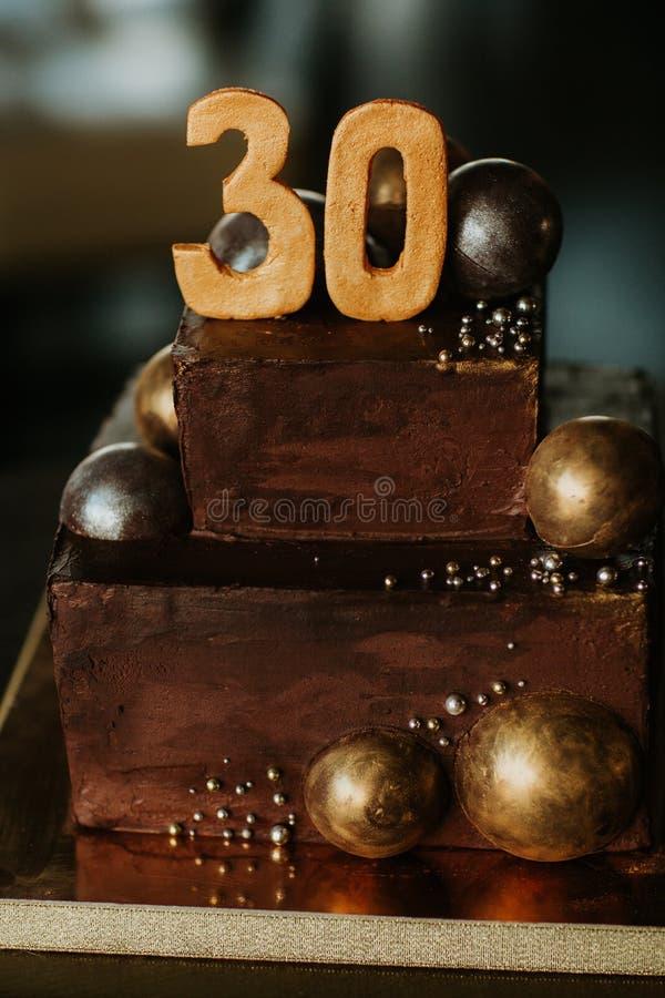 Gâteau de chocolat d'anniversaire avec un numéro trente décoré des boules d'or de chocolat Joyeux anniversaire image stock