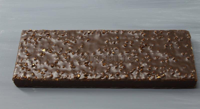 Gâteau de chocolat non coupé avec l'écrou remplissant sur le fond gris-foncé images libres de droits