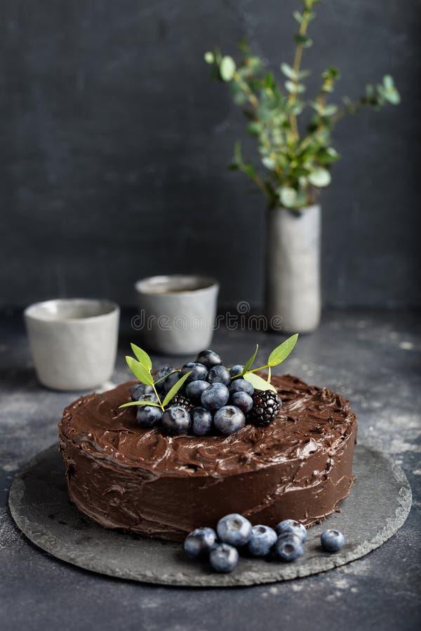 Gâteau de chocolat de vacances avec des tasses sur le fond gris-foncé images libres de droits