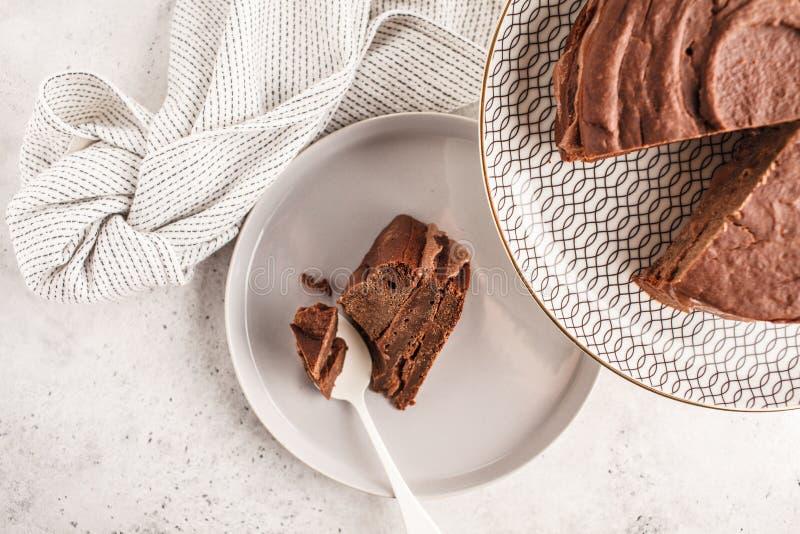 Gâteau de chocolat de Vegan sur un plat blanc pour le gâteau, vue supérieure, PS de copie photographie stock libre de droits