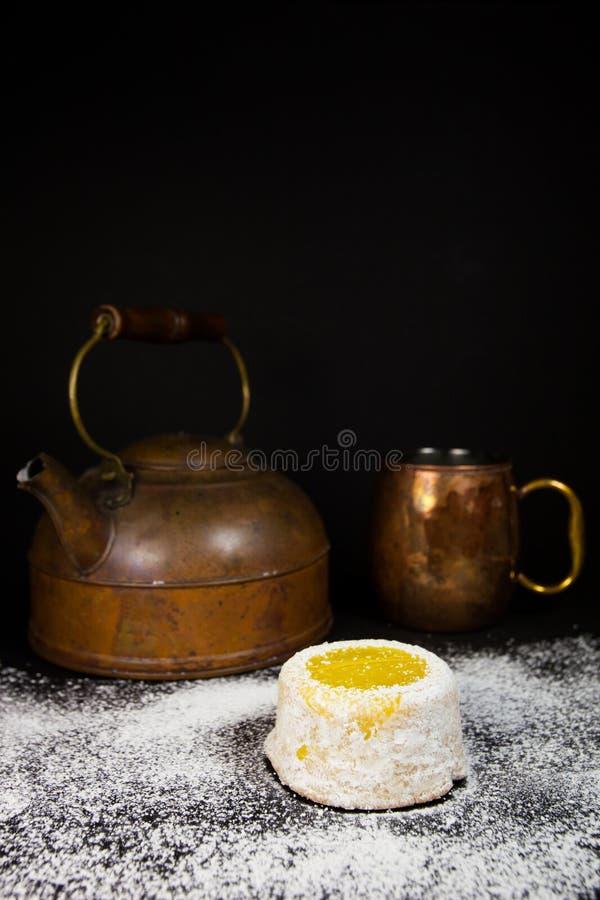 Gâteau de citron avec du sucre en poudre sur le fond foncé avec le pot et la tasse de cuivre de thé images libres de droits