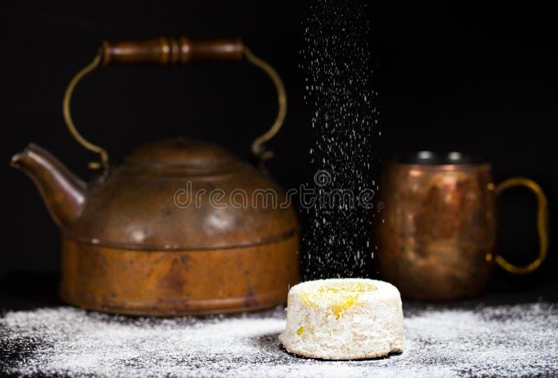 Gâteau de citron avec la bruine en poudre de sucre sur le fond foncé avec le pot et la tasse de cuivre antiques de thé photo stock