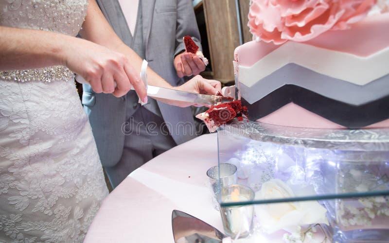Gâteau de coupe de couples de nouveaux mariés image stock