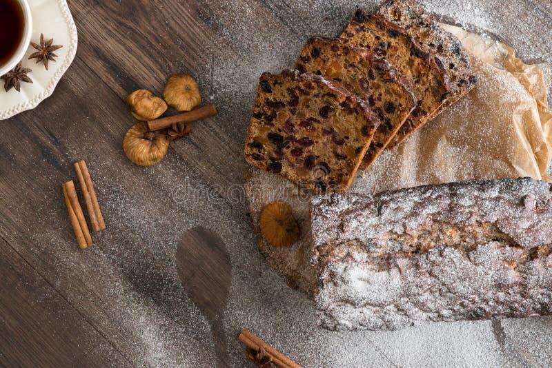 Gâteau de Cristmas de fruits sur la table en bois de brun foncé Cannelle, anis d'étoile, figues et tasse de thé photographie stock libre de droits