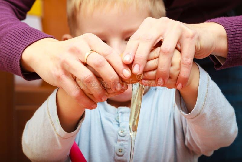 Gâteau de cuisson de petit garçon avec la mère, cassant l'oeuf photo libre de droits