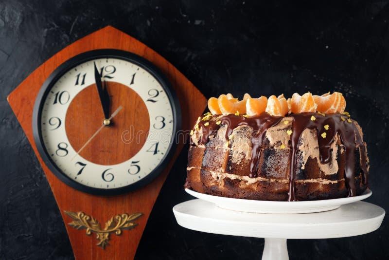 Gâteau de dessert avec le glaçage de chocolat décoré des mandarines sur un fond noir Horloge en bois photo libre de droits