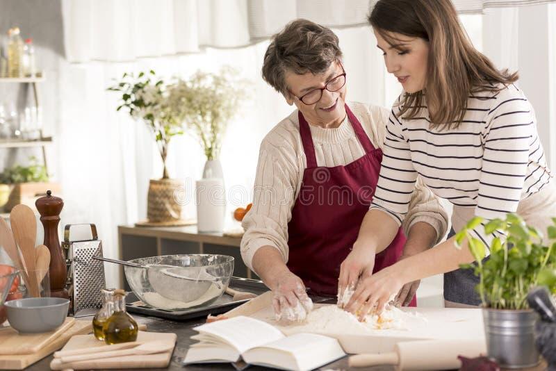 Gâteau de enseignement de cuisson de petite-fille de grand-mère photo libre de droits