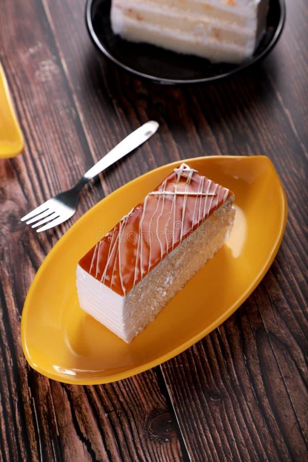 Gâteau de fromage à la pâte de caramel sur une assiette jaune avec de la fourchette sur une table en bois photos stock