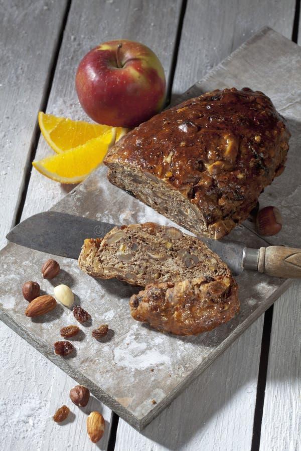 Gâteau de fruits secs de Noël avec des écrous et des fruits sur le conseil en bois photographie stock libre de droits