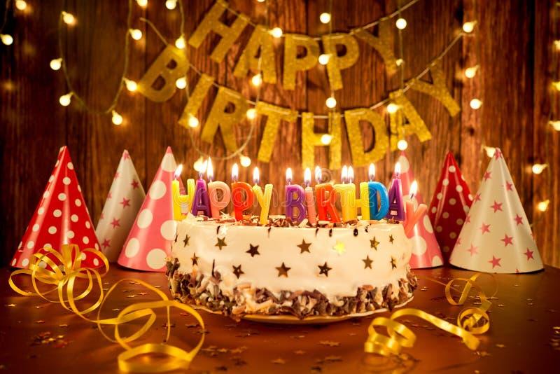 Gâteau de joyeux anniversaire avec des bougies sur le fond des guirlandes a photos libres de droits