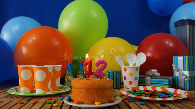 Gâteau de l'anniversaire 12 sur la table en bois rustique avec le fond des ballons colorés, cadeaux, tasses en plastique, plat en photo stock