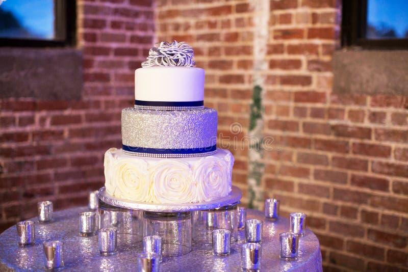 Gâteau de mariage argenté et bleu avec des bougies photographie stock libre de droits