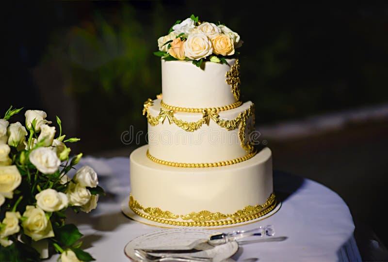 Gâteau de mariage avec des roses de fleurs fraîches Trois rangées image stock