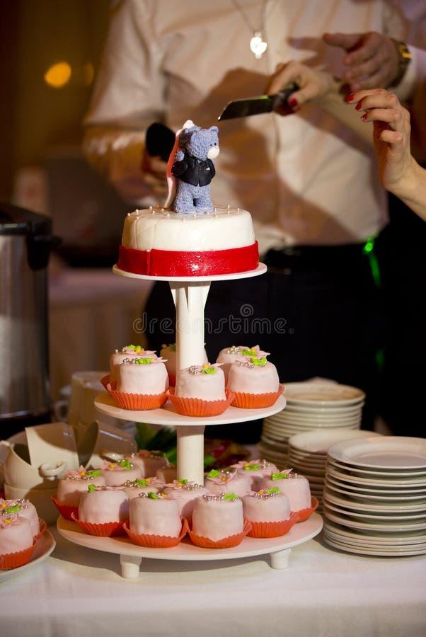 Gâteau de mariage avec les ours et le ruban rouge et couteau dans des mains des jeunes mariés image stock