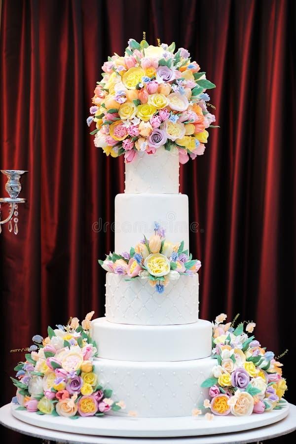 Gâteau de mariage blanc de luxe délicieux décoré des fleurs crèmes images libres de droits