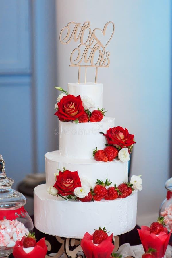 gâteau de mariage blanc de Quatre-couche avec les roses rouges et les fraises photos stock