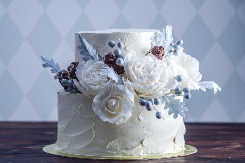 Gâteau de mariage blanc sensible de couchette décoré d'une conception originale utilisant des roses de mastic Concept des dessert images libres de droits