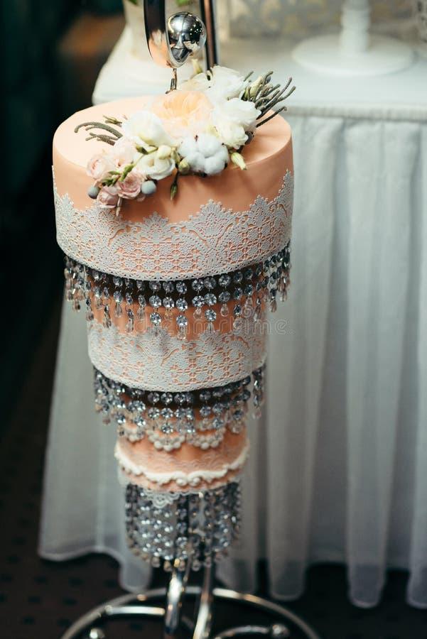 gâteau de mariage orange de Trois-plancher décoré des roses blanches et beiges et des perles accrochantes image stock