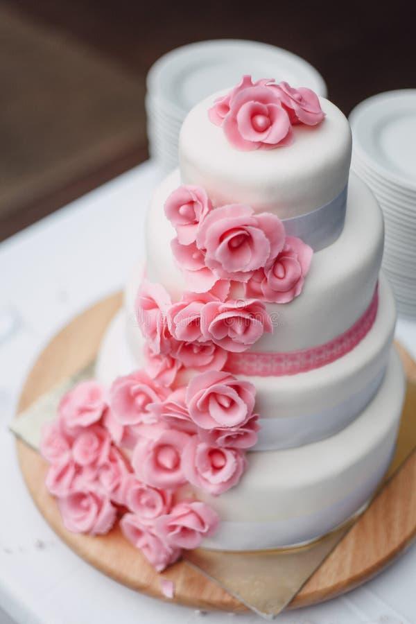 Gâteau de mariage rose blanc avec des roses images stock