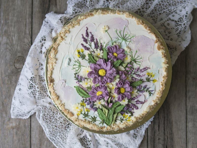 Gâteau de napoléon avec de la crème de vanille, décorée des fleurs de buttercream Type de cru Fond en bois, serviette de dentelle photo stock