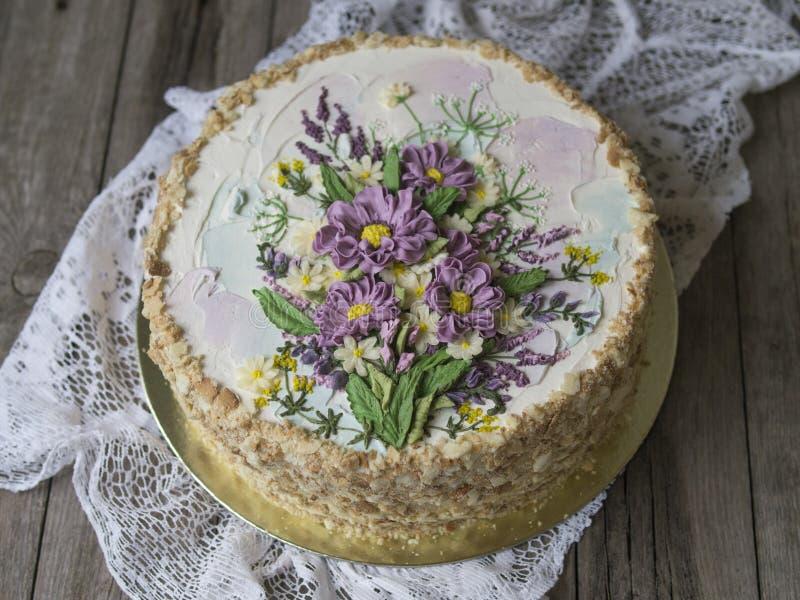 Gâteau de napoléon avec de la crème de vanille, décorée des fleurs de buttercream Type de cru Fond en bois, serviette de dentelle image stock