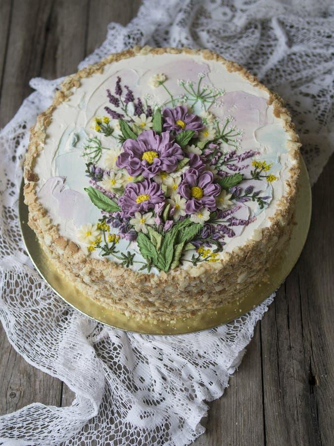Gâteau de napoléon avec de la crème de vanille, décorée des fleurs de buttercream Type de cru Fond en bois, serviette de dentelle photo libre de droits