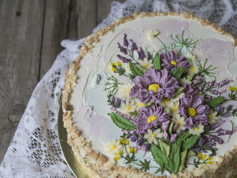 Gâteau de napoléon avec de la crème de vanille, décorée des fleurs de buttercream Type de cru Fond en bois, serviette de dentelle image libre de droits