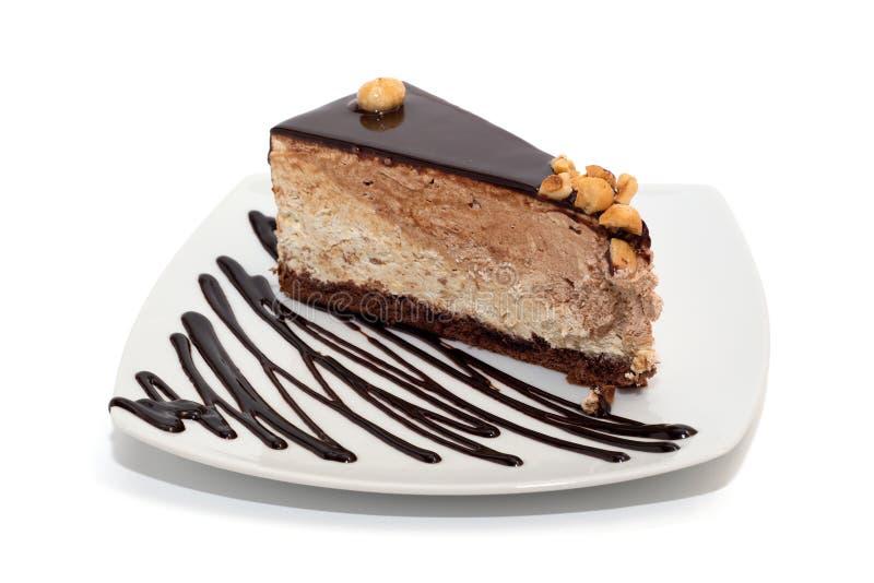 Gâteau de nougat avec du chocolat, les noisettes et l'écrimage d'isolement image libre de droits