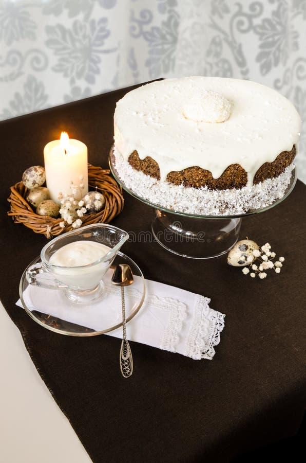 Gâteau de Pâques avec la bougie de glaçage et brûlante crème images stock