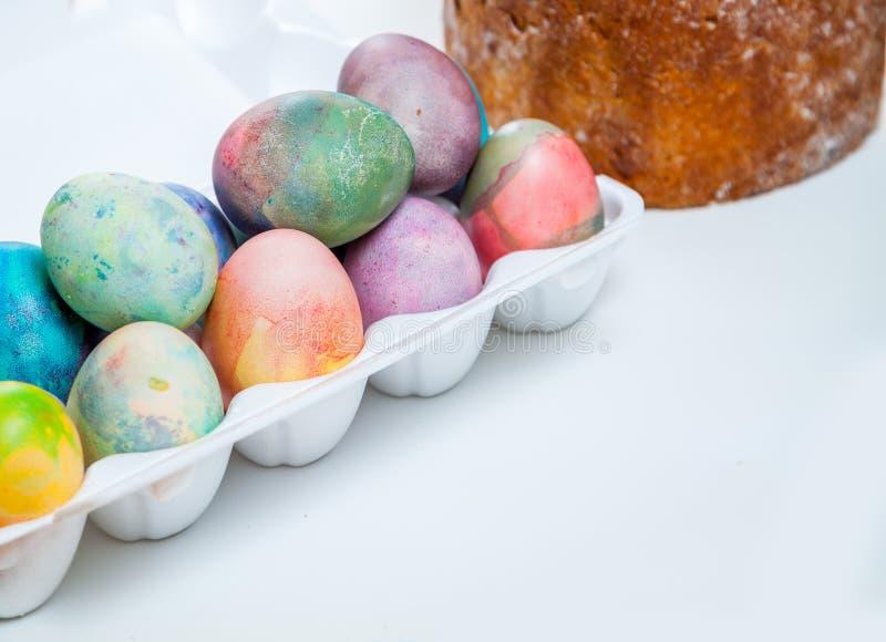 Gâteau de Pâques et oeufs colorés dans le plateau sur le fond blanc photos stock