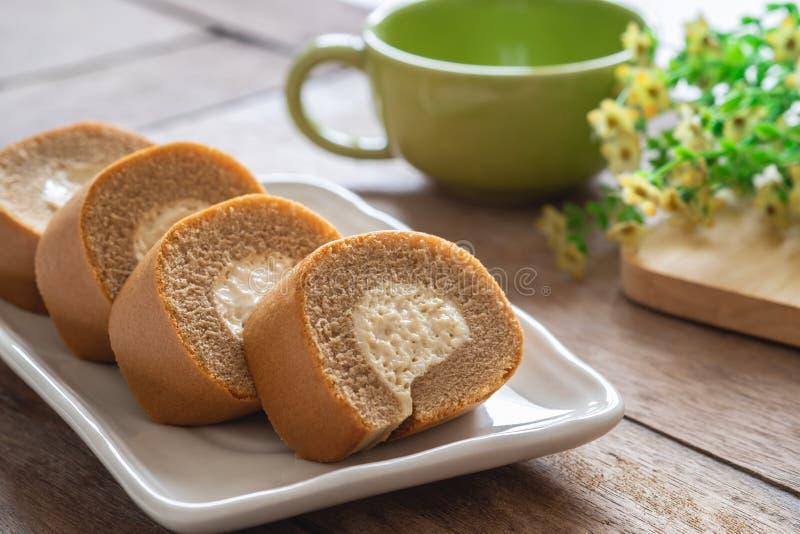 Gâteau de petit pain de café avec de la crème sur la tasse de plat et de café image libre de droits