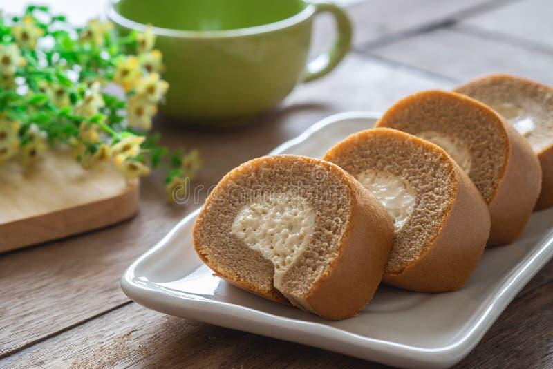 Gâteau de petit pain de café avec de la crème sur la tasse de plat et de café photographie stock libre de droits