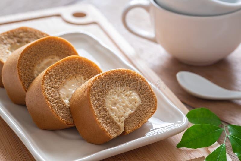 Gâteau de petit pain de café avec de la crème sur la tasse de plat et de café photos libres de droits