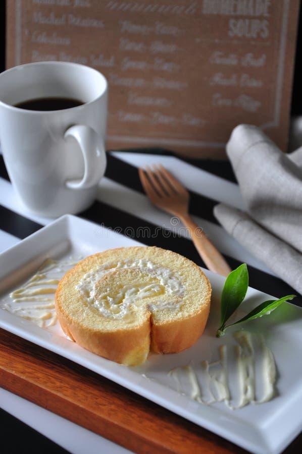 Gâteau de petit pain sur le plat avec du café chaud sur le fond image stock