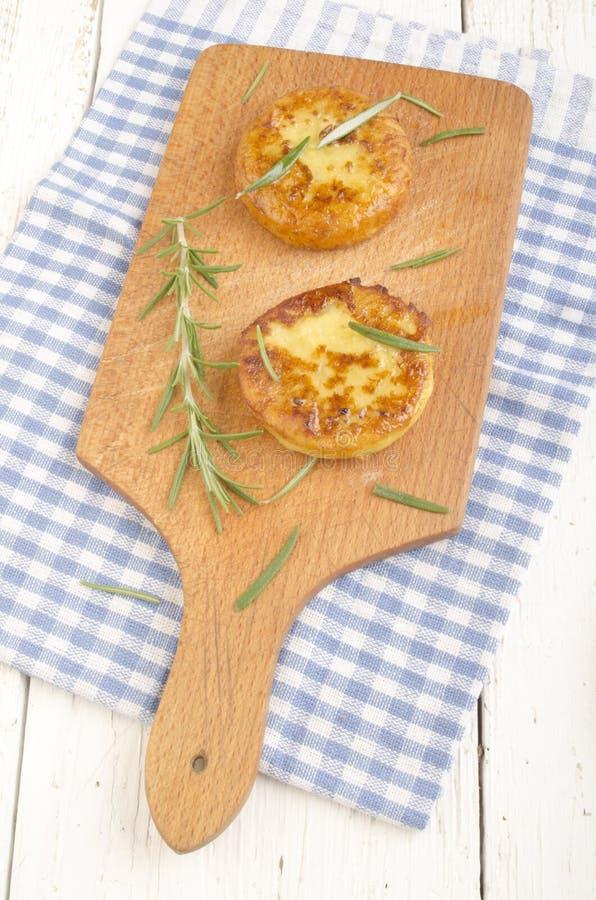 Gâteau de pomme de terre avec le romarin sur le conseil en bois image libre de droits