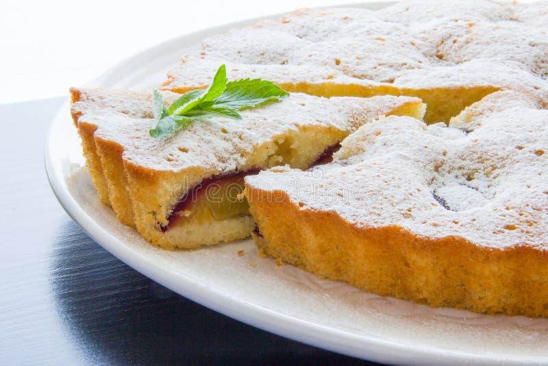 Gâteau de prune épousseté avec du sucre glace, une coupe de tranche images libres de droits