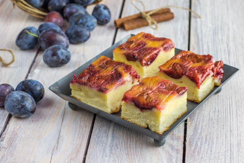 Gâteau de prune avec de la cannelle sur le petit plateau de cuisson sur la table blanche image libre de droits