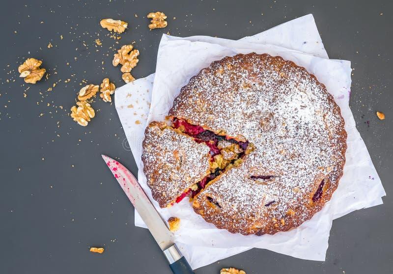 Download Gâteau De Prune Avec Des Noix Sur Un Morceau De Livre Blanc Sur Le Noir Photo stock - Image du poudre, gâteau: 45360664