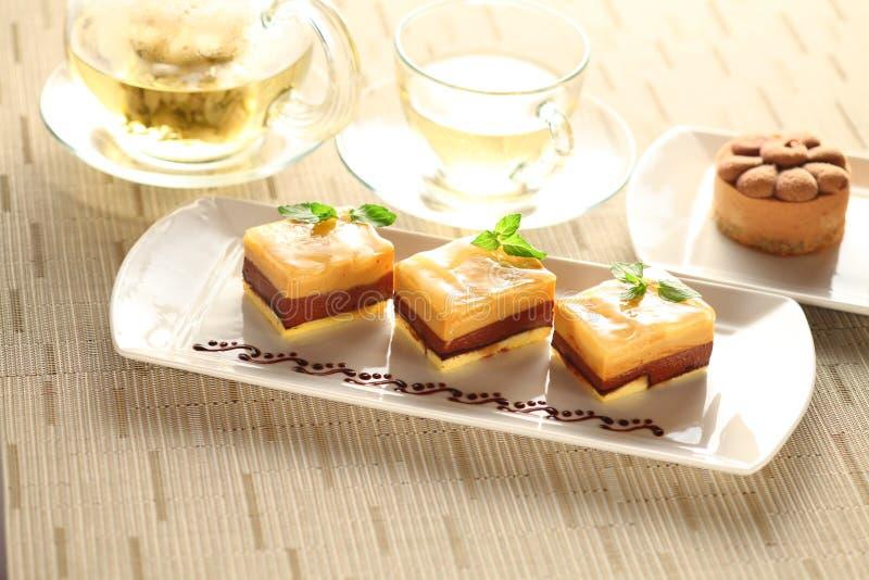 Gâteau de pudding avec les feuilles en bon état du plat blanc avec le thé photo libre de droits