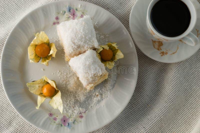 Gâteau de Raffaello avec des tranches sur une assiette avec un café photographie stock libre de droits