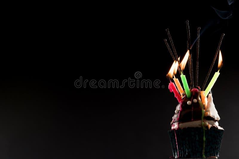 Gâteau de tasse avec des bougies de feu d'artifice et d'anniversaire image libre de droits