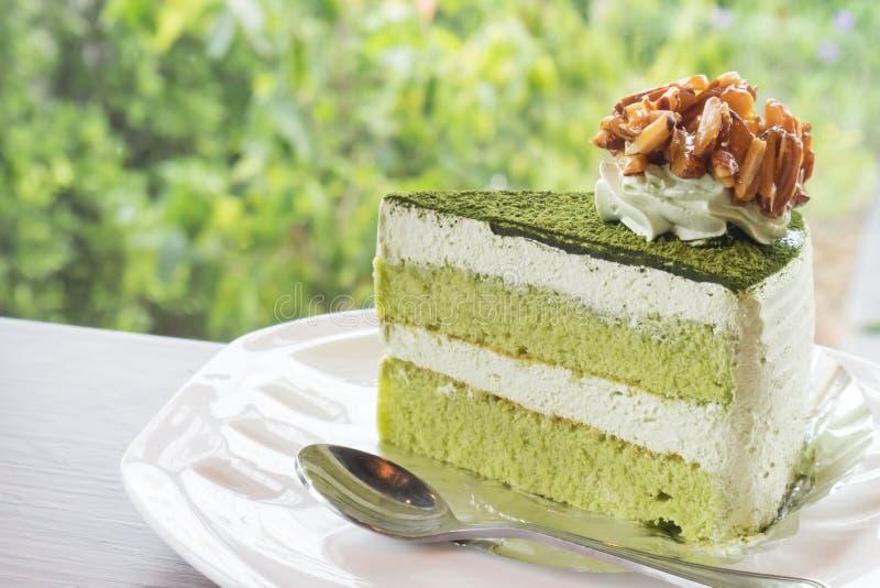 Gâteau de thé vert de matcha de plan rapproché dans le café avec le backgro de nature image stock