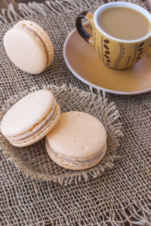 Gâteau des macaronis trois et une tasse de café sur la toile de jute Vue supérieure photographie stock libre de droits