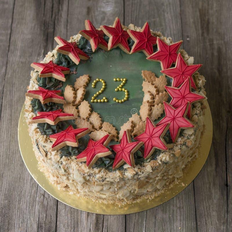 Gâteau doux avec des vacances de décor le 23 février sur le fond en bois clair toned photo stock